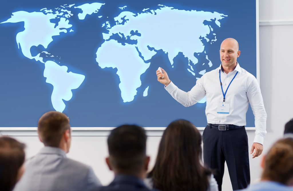 business, education and people concept - smiling businessman or lecturer with world map on projection screen and group of students at conference presentation or lecture